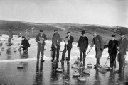 Group of men on beach with curling stones