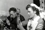 Nurse holds test tube, soldier looks through microscope